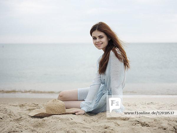 Smiling Caucasian woman sitting on beach
