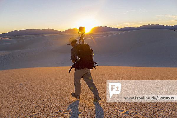 Caucasian man carrying camera and tripod in desert
