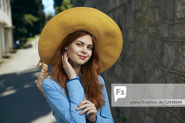 Smiling Caucasian woman wearing hat near stone wall