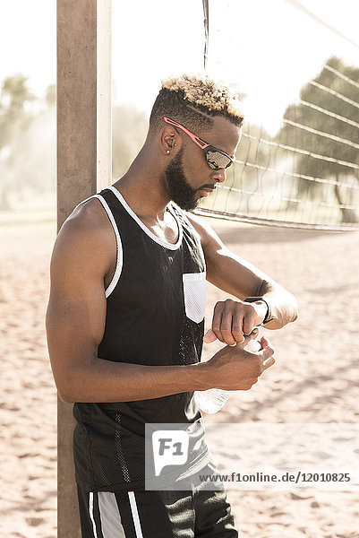 Black man leaning on beach volleyball net checking the time