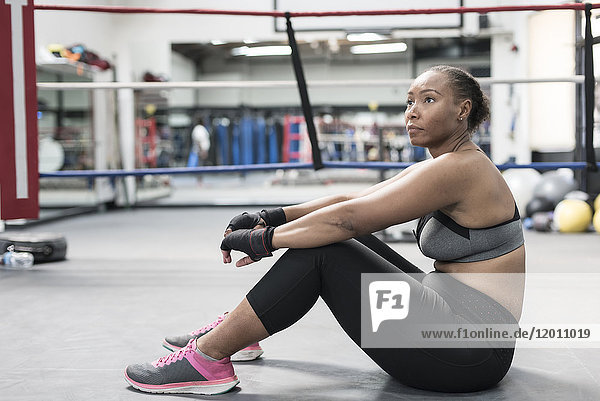 Black woman sitting on floor in boxing ring