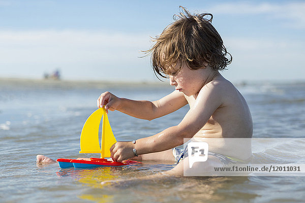 Caucasian boy sitting in ocean playing with toy sailboat