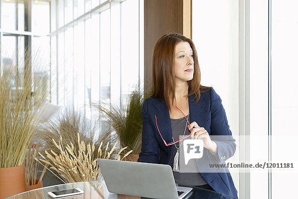 Caucasian businesswoman using laptop and holding eyeglasses