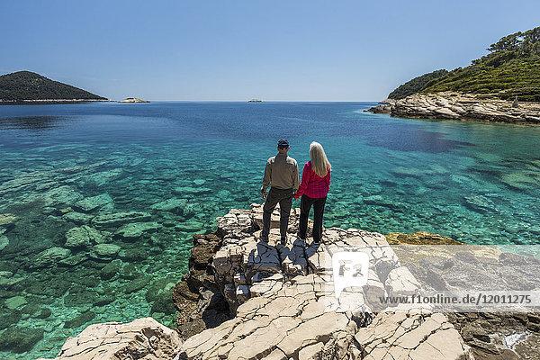 Caucasian couple standing on rock admiring lake