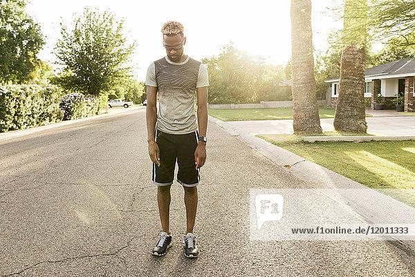 Black man standing on street in the neighborhood looking down