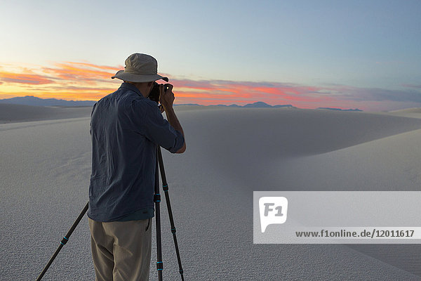 Caucasian man photographing desert at sunset