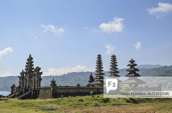 Balinesischer Hindu-Tempel  traditionelle Architektur und hohe Türme mit abgestuften  spitz zulaufenden Dächern in einem Tal am Bratan-See.