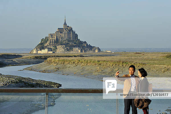 France  Lower Normandy Region  Manche Department  Mont St-Michel seen from the dam on Couesnon river  couple of Asian visitors taking a Selfie.