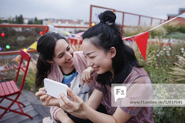 Glückliche Frau  die eine Freundin mit einem Smartphone auf der Terrasse ansieht.