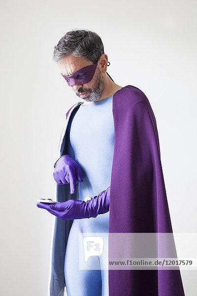 Superheld mit Smartphone auf weißem Hintergrund