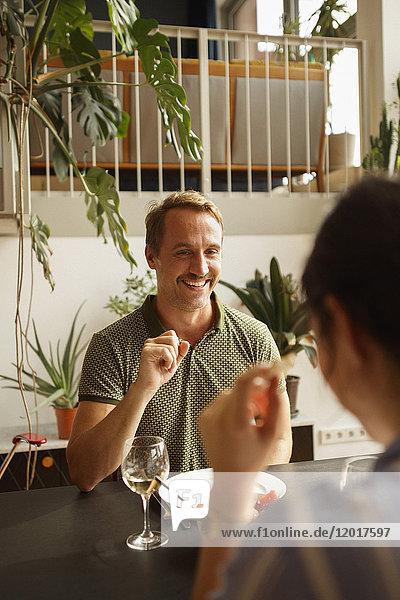 Glücklicher Mann  der die Frau beim Essen am Esstisch im Haus ansieht.