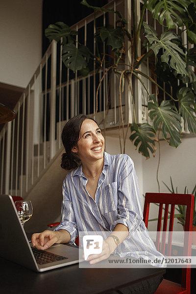 Fröhliche junge Frau schaut weg  während sie den Laptop zu Hause benutzt.