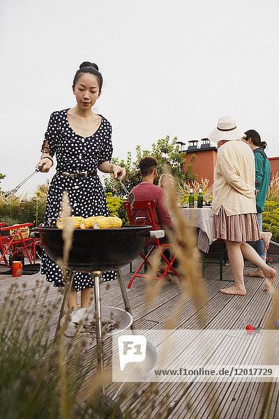 Junge Frau beim Grillen auf der Terrasse mit Freunden im Hintergrund