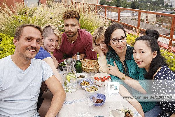 Porträt von glücklichen Freundinnen und Freunden  die am Außentisch auf der Terrasse sitzen.