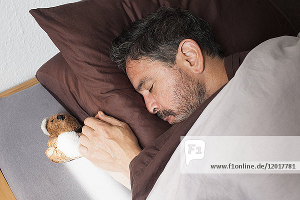Hochwinkelansicht des erwachsenen Mannes  der von einem kleinen Teddybären auf dem Bett zu Hause schläft.