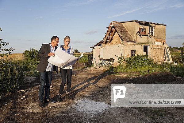 Frau steht mit Immobilienmaklerin beim Lesen von Dokumenten gegen Haus am sonnigen Tag