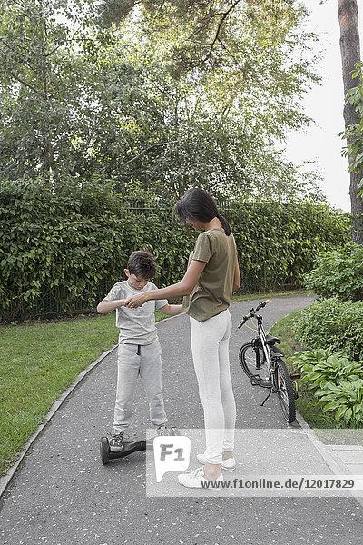 Mutter unterstützt den Sohn bei der Verwendung eines selbstausgleichenden Brettes auf der Straße gegen Pflanzen.