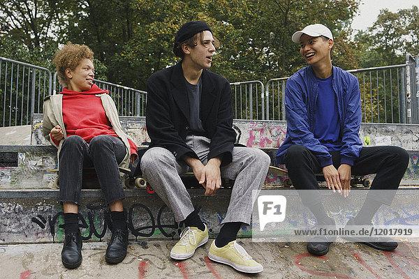 Volle Länge von lächelnden Freunden  die auf einer Treppe im Park sitzen und sich unterhalten.