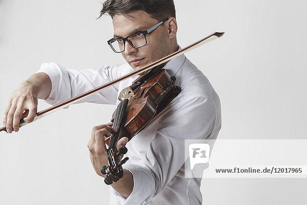 Sicherer junger Mann spielt Geige vor weißem Hintergrund