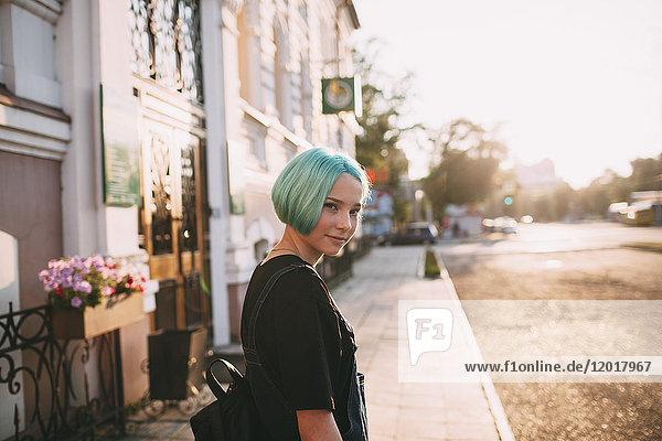 Porträt eines lächelnden Teenagermädchens  das an einem sonnigen Tag auf dem Bürgersteig in der Stadt steht.