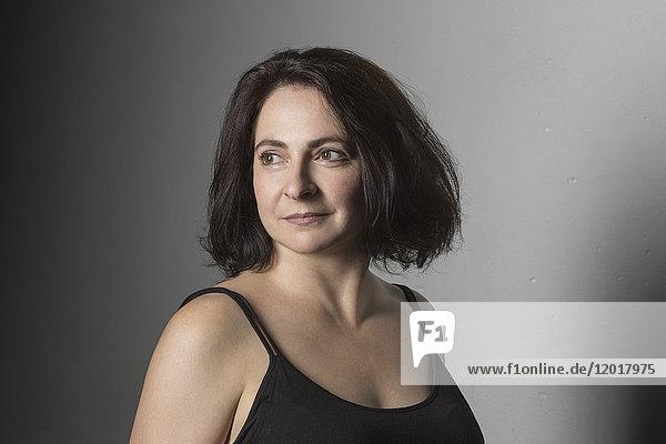 Nahaufnahme einer nachdenklichen reifen Frau mit kurzen Haaren vor grauem Hintergrund