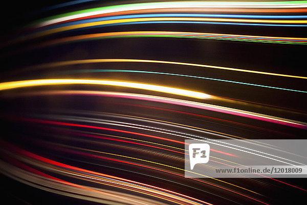 Vollbildabstraktes Bild verschiedener Lichtspuren vor schwarzem Hintergrund