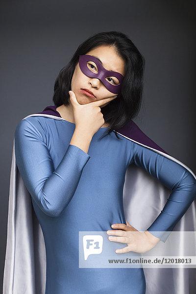 Nachdenkliche junge Frau im Superheldenkostüm stehend mit der Hand auf der Hüfte vor grauem Hintergrund.