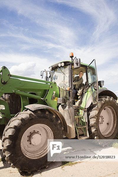 Tiefblick auf die reife Frau  die den Traktor gegen den Himmel fährt.
