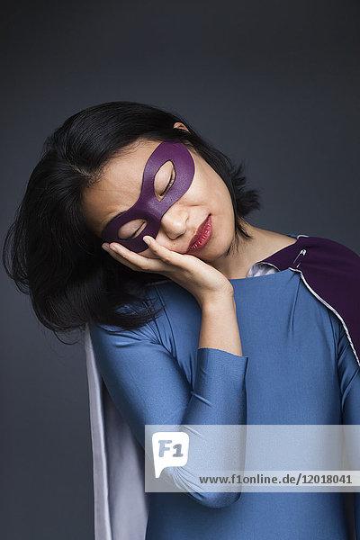 Weibliche Superheldin schlummert vor grauem Hintergrund