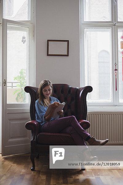 Schöne junge Studentin sitzt auf einem Sessel und liest zu Hause ein Buch.