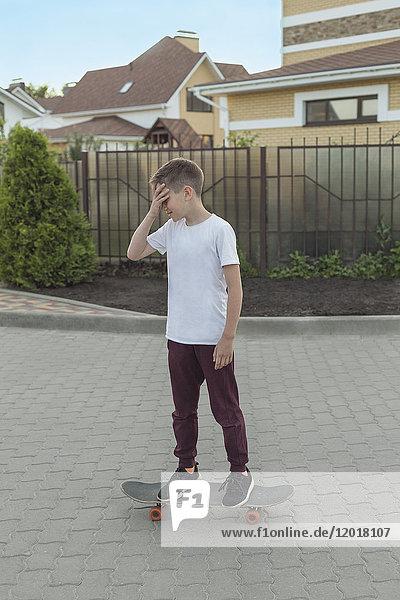 Junge auf Skateboard auf Fußweg gegen Häuser