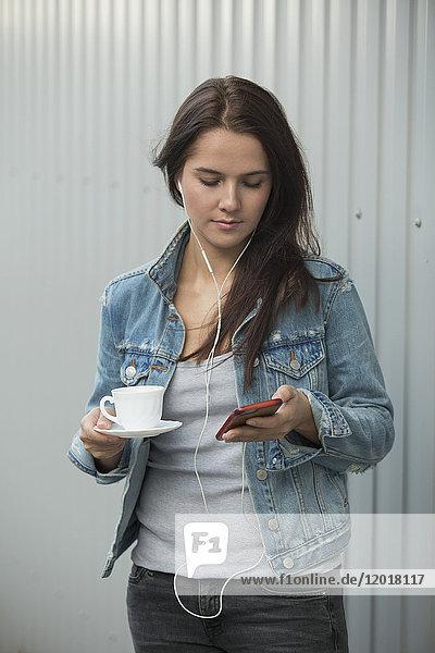 Schöne Frau  die das Handy benutzt  während sie die Kaffeetasse an die Metallwand hält.