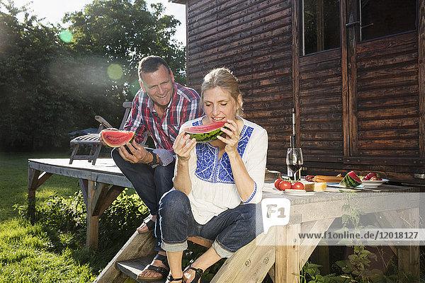 Ein glückliches reifes Paar  das an einem sonnigen Tag vor dem Bauernhaus sitzt und die Wassermelonenscheibe genießt.