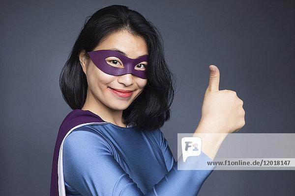 Porträt einer selbstbewussten Superheldin  die vor grauem Hintergrund die Daumen nach oben bewegt.