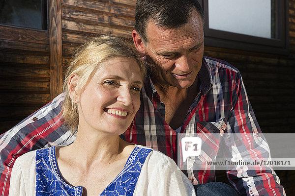 Lächelndes reifes Paar vor dem Bauernhaus sitzend