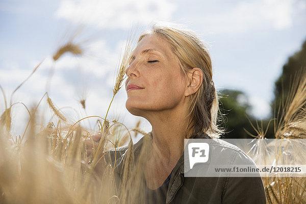 Nachdenklich lächelnde Frau mit geschlossenen Augen  die sich an einem sonnigen Tag inmitten von Getreide auf dem Bauernhof ausruht.