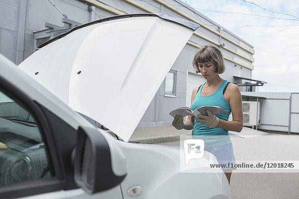 Reife Frau beim Lesen der Bedienungsanleitung im Stehen am Pannenfahrzeug
