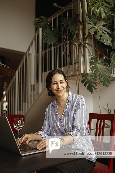 Portrait of smiling young woman using laptop at home