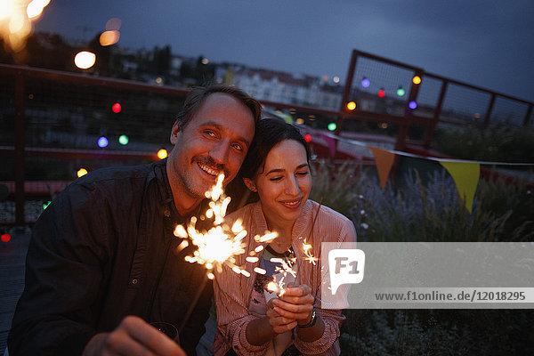 Glückliches Paar  das nachts auf der Terrasse funkelt.