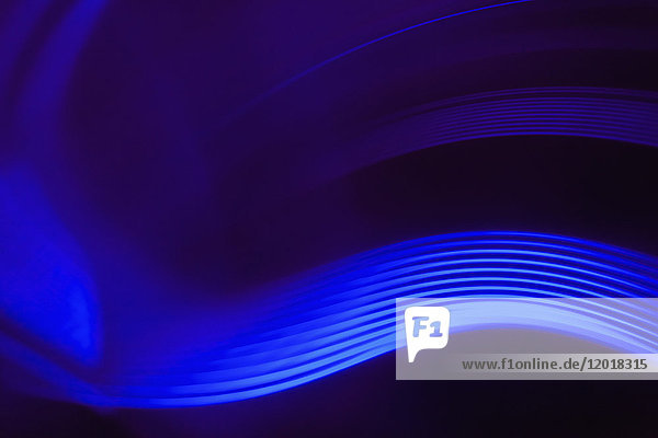 Abstrakte Nahaufnahme von leuchtend blauen Lichtspuren vor schwarzem Hintergrund