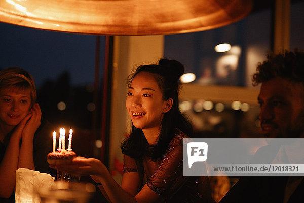 Glückliche Frau hält kleinen Geburtstagskuchen mit angezündeten Kerzen  während sie bei Freunden zu Hause sitzt.