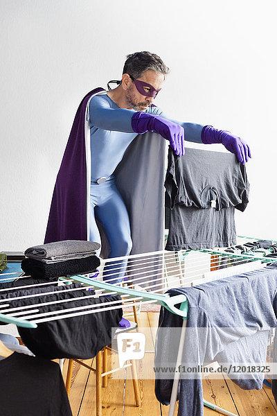 Reife Superhelden trocknende Wäsche auf Gestell gegen weiße Wand