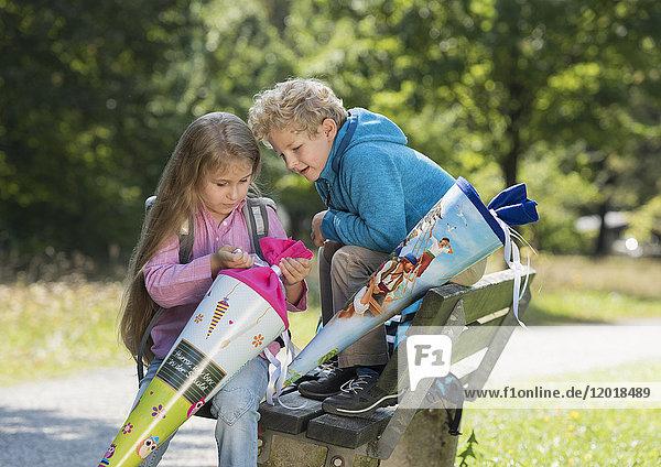 Zwei Kinder packen Schultüte aus