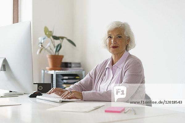 Porträt einer lächelnden Frau  die im Büro an der Wand sitzt.
