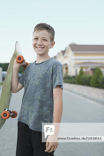 Porträt eines lächelnden Jungen mit Skateboard im Stehen auf der Straße