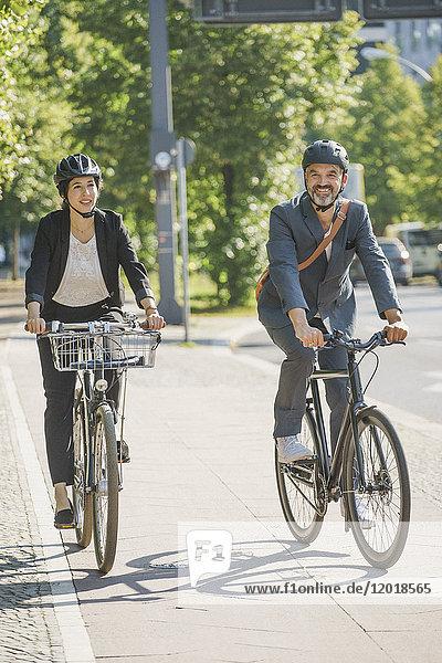 Geschäftskollegen mit dem Fahrrad auf der Straße in der Stadt bei strahlendem Sonnenschein