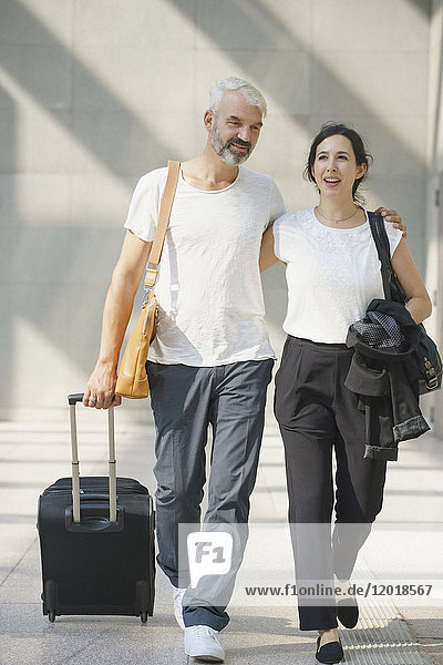Volle Länge des Geschäftspaares mit Rollgepäck zu Fuß am Flughafen