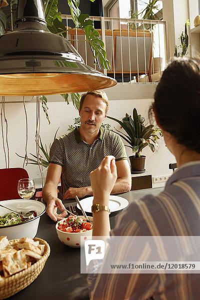 Paar mit Essen am Esstisch im Haus