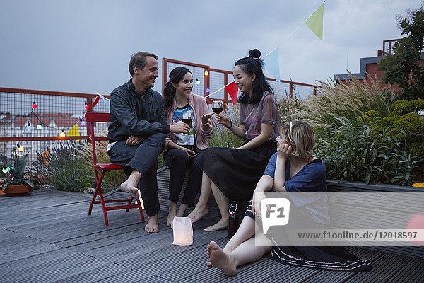 Freunde unterhalten sich  während sie in der Abenddämmerung auf der Terrasse Weingläser halten.