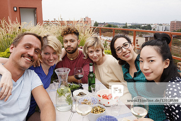 Porträt von glücklichen Freunden am Außentisch auf der Terrasse